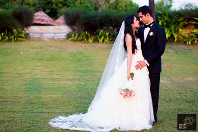 White off-shoulder wedding dress by Vera Wang styled with white and pink carnation bouquets