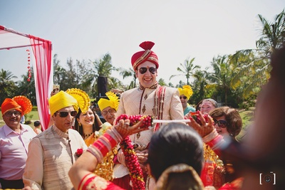 Traditional fun at varmaala ceremony as the groom is lifted high on his friends shoulder