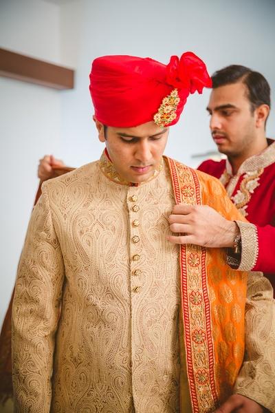 Beige textured gold button embellished sherwani styled with red Safa and orange dupatta
