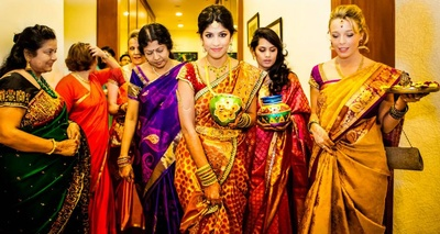 Dressed in an intricately woven gold and red kanjivaram silk saree