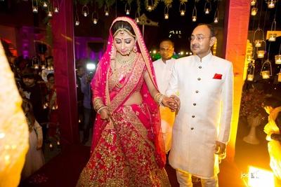Pink bridal lehenga embellished with gold sequined motifs and polki necklace set by Sabysachi Mukherjee