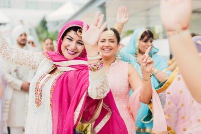 The dancing baraat enters the wedding mandap arena