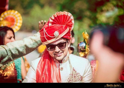 Ivory wedding sherwani styled with a red safa embellished with a pleated top and a kalgi