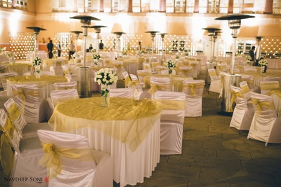 Clustered seating arrangement with gold table covers, Rose bouquets held in a crystal glass vase are used as centerpieces