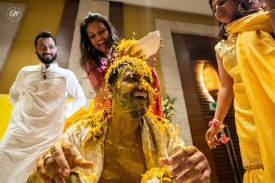 a candid capture of the groom enjoying at his haldi ceremony