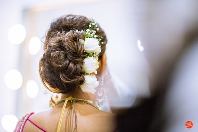 Bridal hair do for the wedding ceremony with white roses and a floral bun