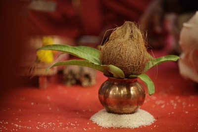Ceremonial prepartions; Shrifal and Mango leaves on a Kalash based on rice grains, setup for the Gruh-pravesh ceremony