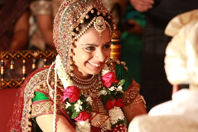 Bride decked in layers of jewellery. Choker studded with kundan and gemstones, Raanihaar, borla maathapatti, nose ring, earrings, armlet and bangles