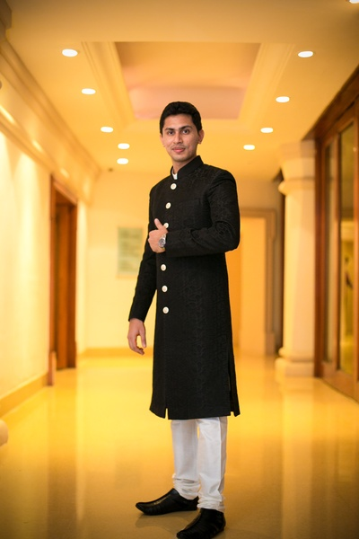 Black textured achkan with button detailing and styled with white churidaar and shoes