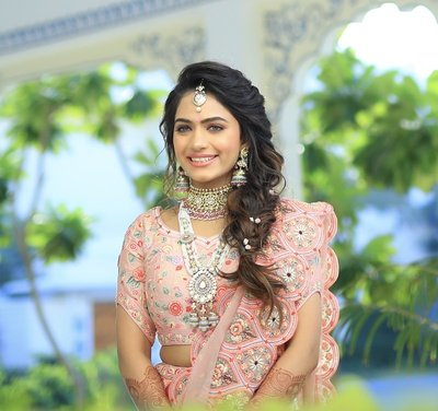 The pretty bride in a blush pink and ice blue lehenga with a scalloped  dupatta