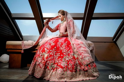 Traditional bride posing in her red lehenga for the wedding function