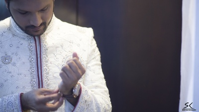 The Groom wearing a white and red high-necked sherwani with intricate thread work and stones