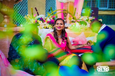 Beautiful bride Shruti dressed in a pink and yellow outfit for her outdoor mehndi ceremony