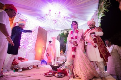 Mushroom style draped mandap adorned with chandelier and foral walls