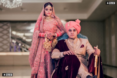 Wedding portrait of the couple post wedding. The groom sports a velvet shawl as part of this attire while the bride stands tall in her pink lehenga and golden jewellery