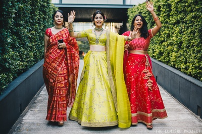 Three gorgeous ladies, flaunting peppy and vibrant lehengas and grooving towards the wedding venue!