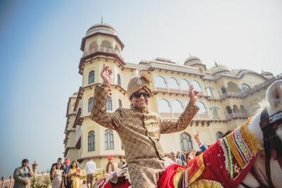 Wearing dark beige sherwani with color coordinated turban .