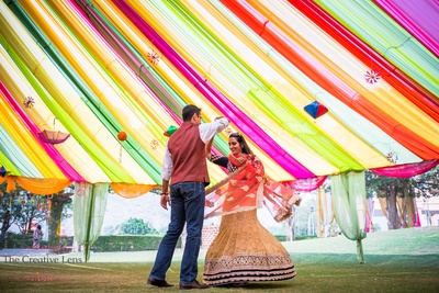 Colorful drapes adorned with upturned umbrella, topiaries and paper fans