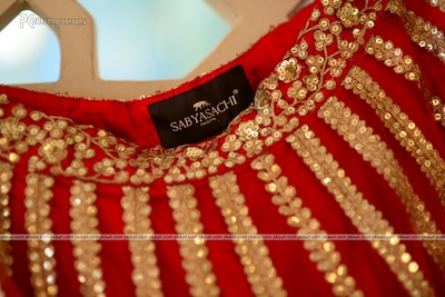 Red wedding lehenga embellished with gold sequins by Sabysachi