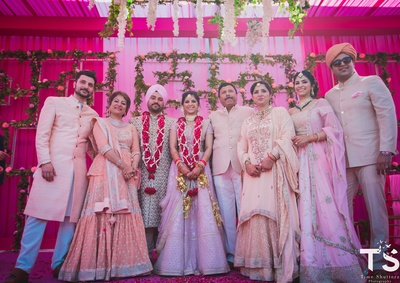 The couple poses with their family as husband and wife