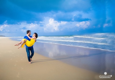 Romantic pre wedding photo shoot by the beach dressed in bright yellow and blue outfits