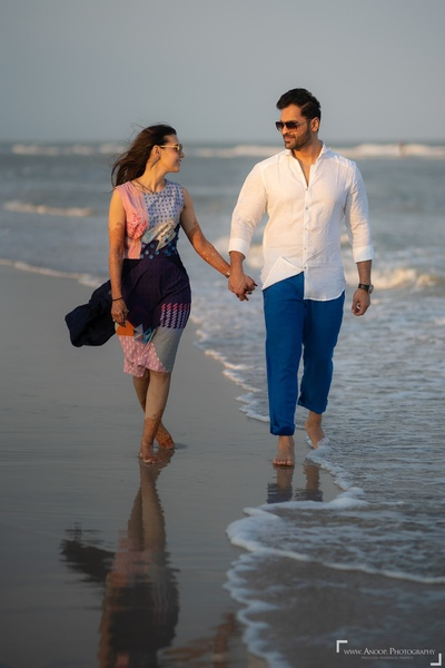 The couple taking a romantic walk by the ocean as part of their pre-wedding photo shoot.