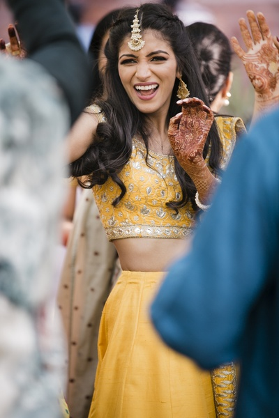 The bride looks like she is having a gala time dancing at her mehendi ceremony!