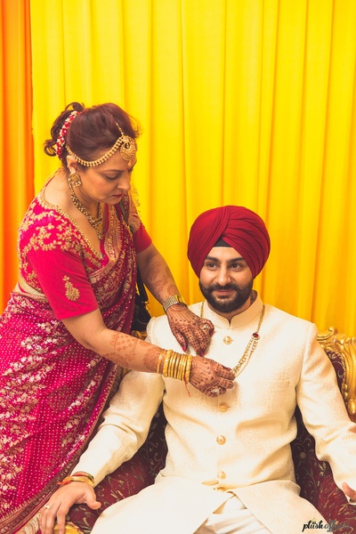 Groom's mother helping him get ready for the wedding function