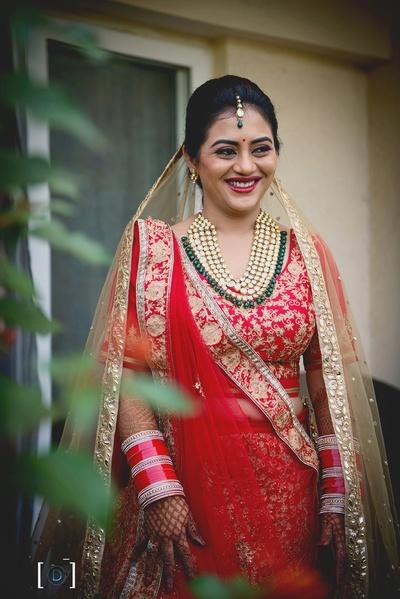 the bride stuns in her red Meena Bazaar lehenga and kundan jewellery