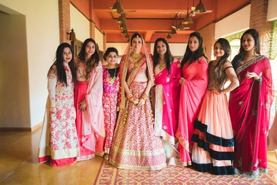 Bridesmaids dressed up in pink and peach outfits for the wedding day.