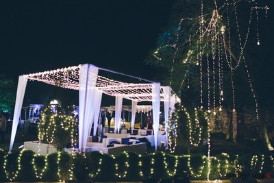 Cabana setup for an outdoor evening event with white drapes and series of fairy lights