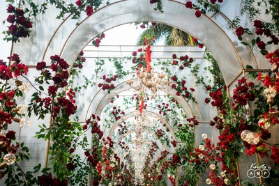 A beautiful archway replete with roses and chandeliers leading to the venue.