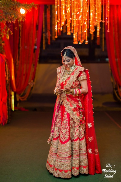 Elegant red and golden bridal lehenga with broad and heavy boarders paired with stunning jewelery and tussels