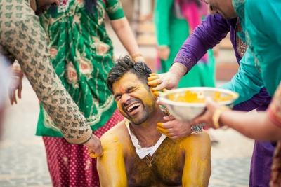 family has fun during the haldi ceremony with  the groom !