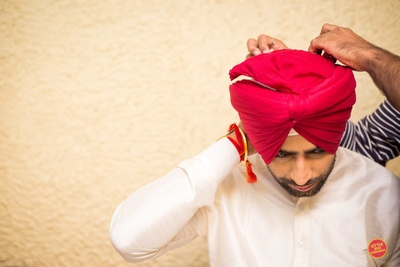 The groom being helped to tie his turban