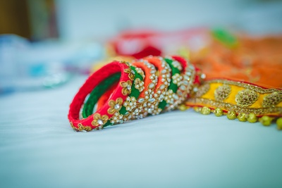Bridal green, red and orange bangles adorned with stones, beads and zari work