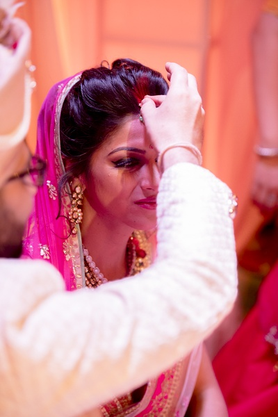 The groom putting sindoor on the bride's forehead.