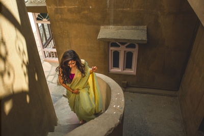 the bride in a jade green saree moments before she starts getting ready for her wedding