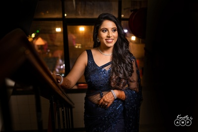the bride looks stunning in a navy blue net saree for her reception