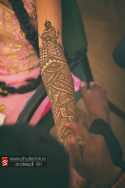 Bride's arms being patterned with Indian mehendi design