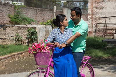 Pre-wedding shoot pastel pink bicycle prop with a basket filled with baby pink and red Roses