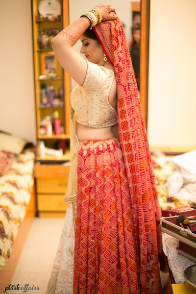White and golden brocade lehenga paired with red bandhej print dupatta!
