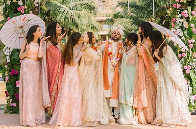 Bride and groom pose along with their friends at the wedding function
