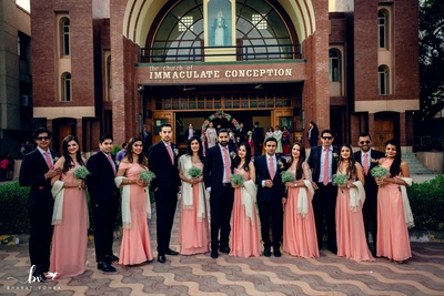 Groomsmen and bridesmaids pose at the wedding ceremony.