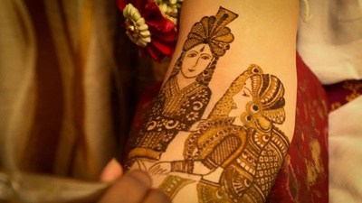 Bridal arms being patterned with portraits of bride and groom