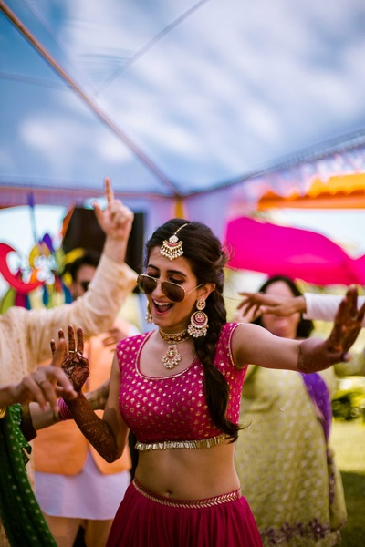 Traditional bride dancing with friends and family during the mehndi function at The Lalit Golf and Spa Resort, Goa