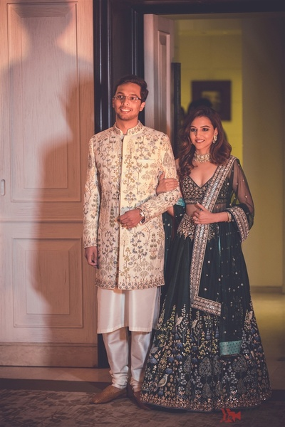 Benaisha Kharas in an emerald green lehenga embellished with intricate, hand painted pichhwai work and Yash in coordinated pichwai work sherwani by Anita Dongre for their sangeet