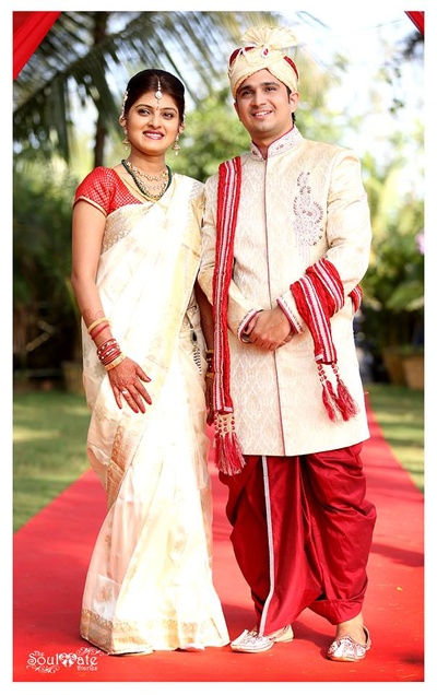 Groom wearing a cream wedding Sherwani styled with a red silk dhoti and a matching dushala