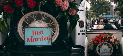 White vintage car decorated with clustered floral bouquets and a quirky tag