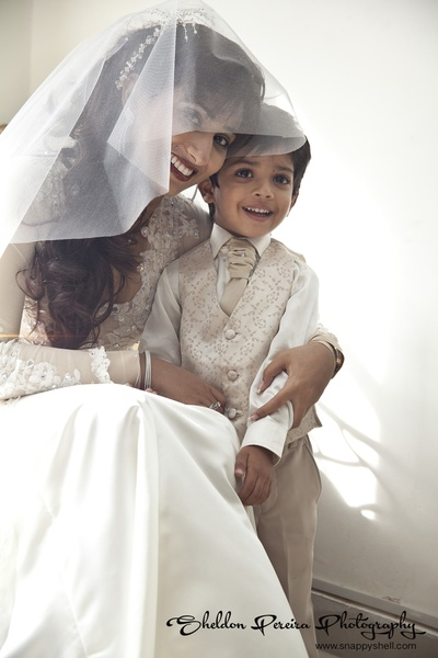 Gorgeous bride with the page-boy dressed in a beige-gold suit